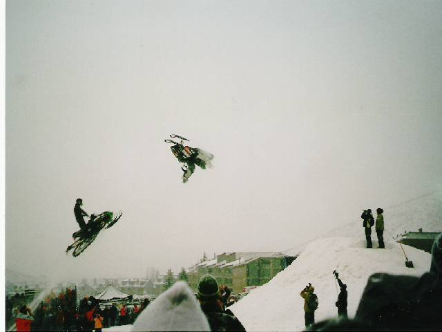 backflip on a snowmobile with someone right on his tail