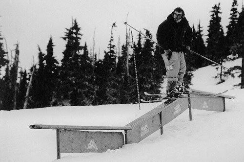 Downhill skier sliding sideways on metal structure