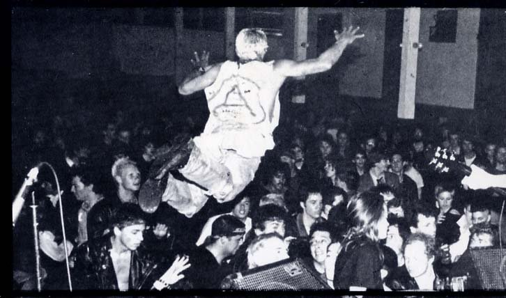 This is a photo of a dude doing a nice stagedive at a norther Cal. PunK gig early 80's