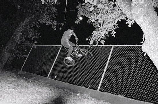 riding a bike on a fence