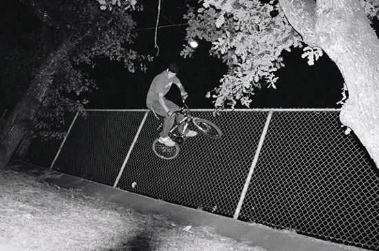 riding a bike on a fence