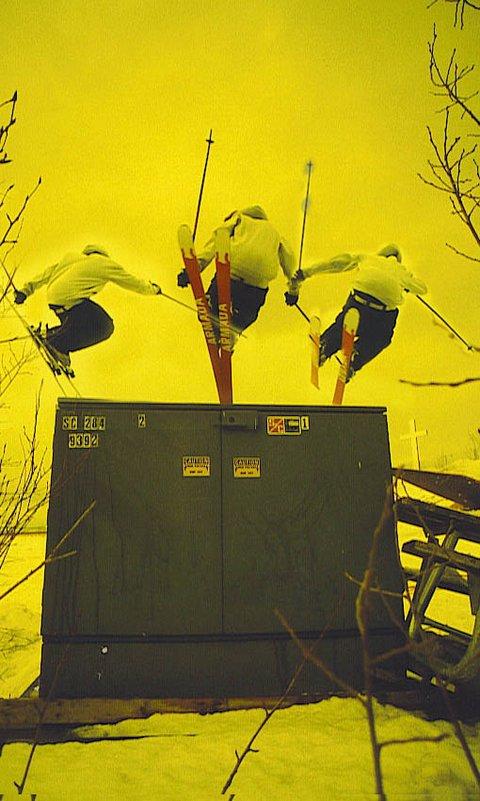 Josh skiing over a box