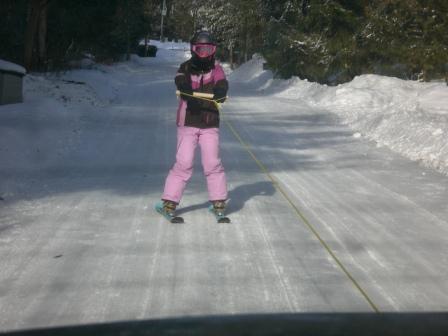 Little sister skiing behind car