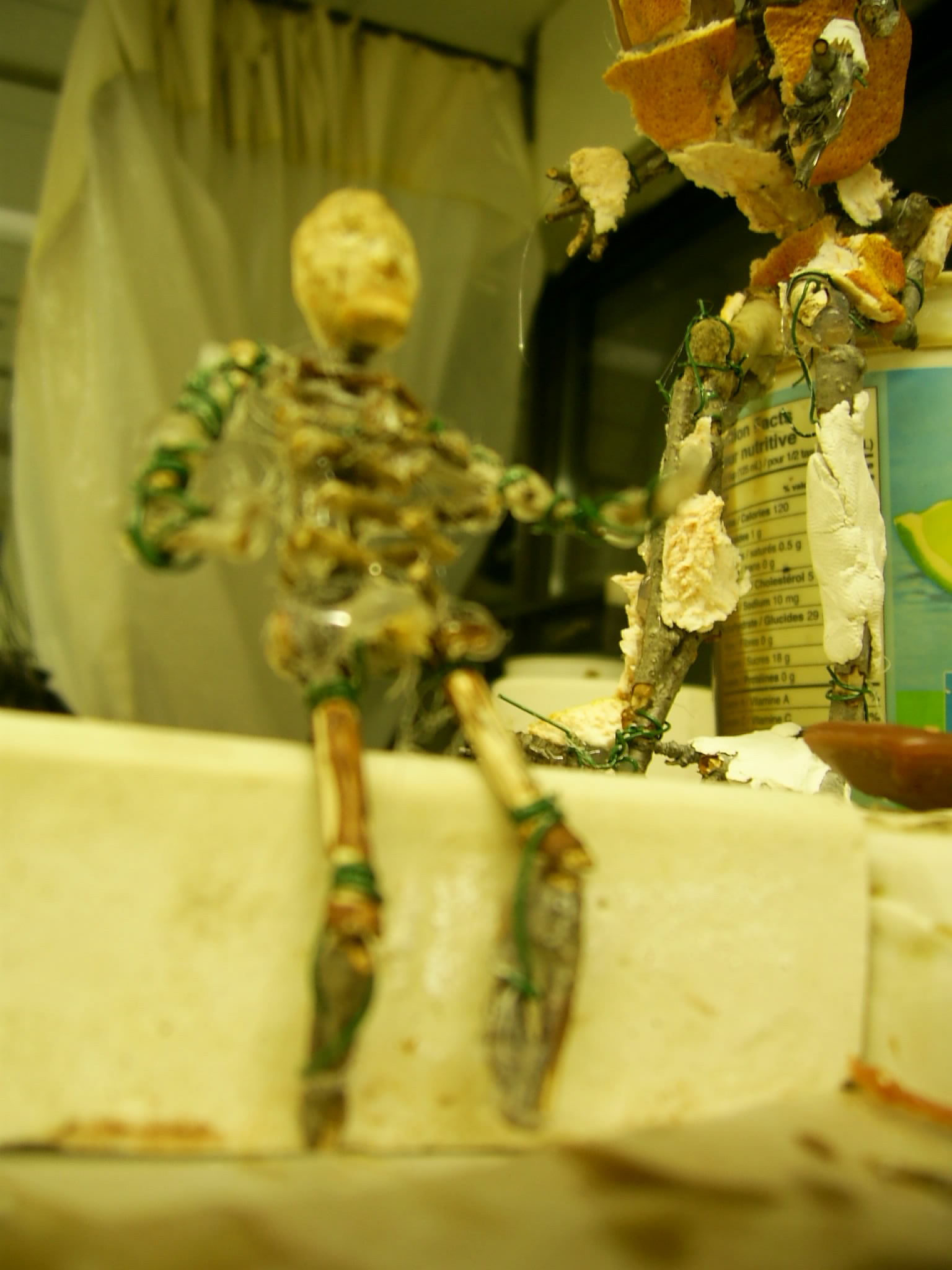 1 of 3 tiny men I made for class, with large scale maquette in background