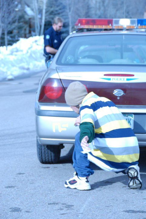 Fletcher putting NS sticker on cop car